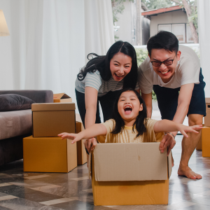happy-asian-young-family-having-fun-laughing-moving-into-new-home-japanese-parents-mother-father-smiling-helping-excited-little-girl-riding-sitting-cardboard-box-new-property-relocation